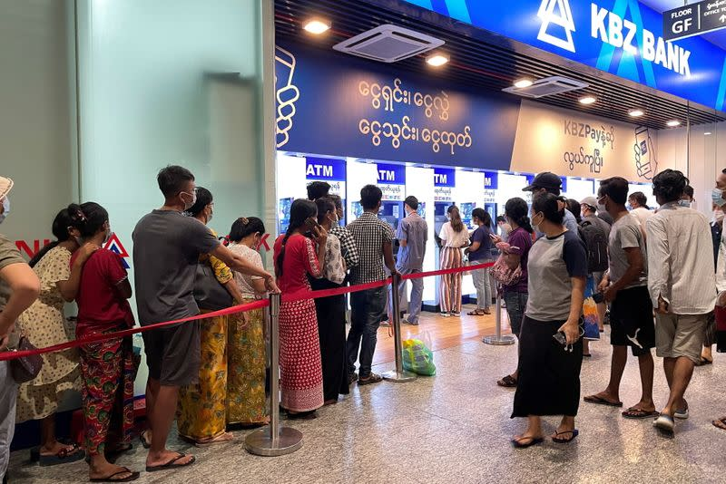 People line up in front of ATM's machines to withdraw cash, in Yangon