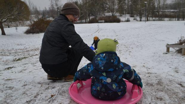 A dad and his son go sledding in the snow.