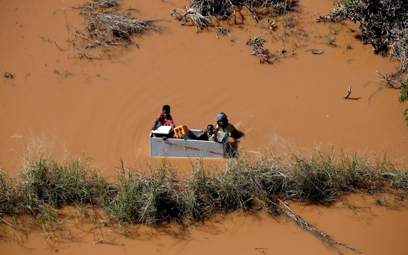 A family use a fridge as transport after Cyclone Idai - REUTERS
