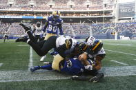 Hamilton Tiger-Cats linebackers Tyrice Beverette (28) and Curtis Newton (44) tackle Winnipeg Blue Bombers' Noah Hallett (23) during the first half of a Canadian Football League game Thursday, Aug. 5, 2021, in Winnipeg, Manitoba. (John Woods/The Canadian Press via AP)