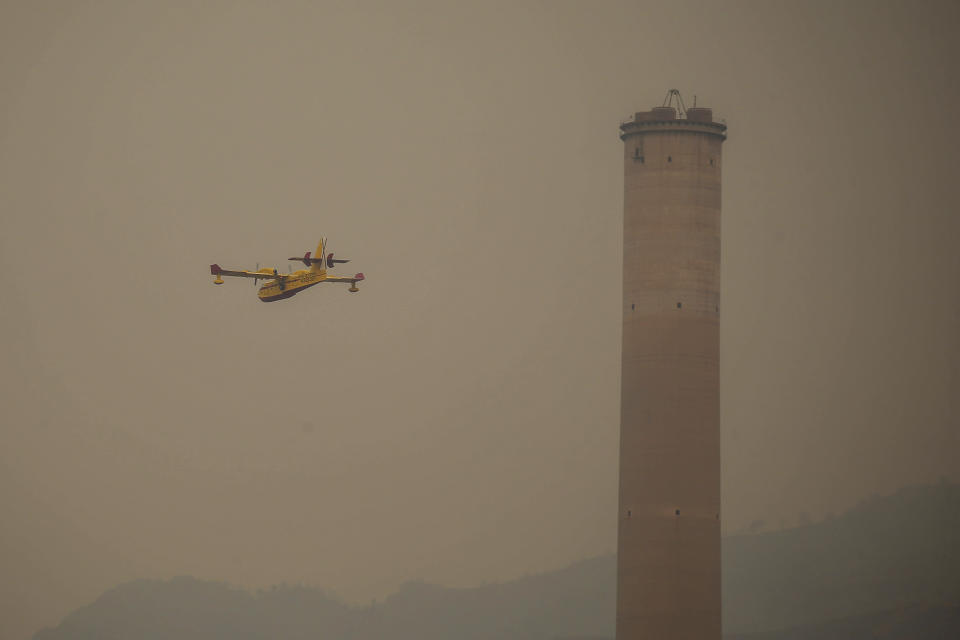 A Spanish firefighting plane pours water on a fire near the Kemerkoy Power Plant, a coal-fueled power plant, in Milas, Mugla in southwest Turkey, Thursday, Aug. 5, 2021. A wildfire that reached the compound of a coal-fueled power plant in southwest Turkey and forced evacuations by boats and cars, was contained on Thursday after raging for some 11 hours, officials and media reports said. (AP Photo/Emre Tazegul)
