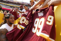 Washington Football Team defensive end Chase Young (99) signs autographs for fans before an NFL football game against the Los Angeles Chargers, Sunday, Sept. 12, 2021, in Landover, Md. (AP Photo/Andrew Harnik)