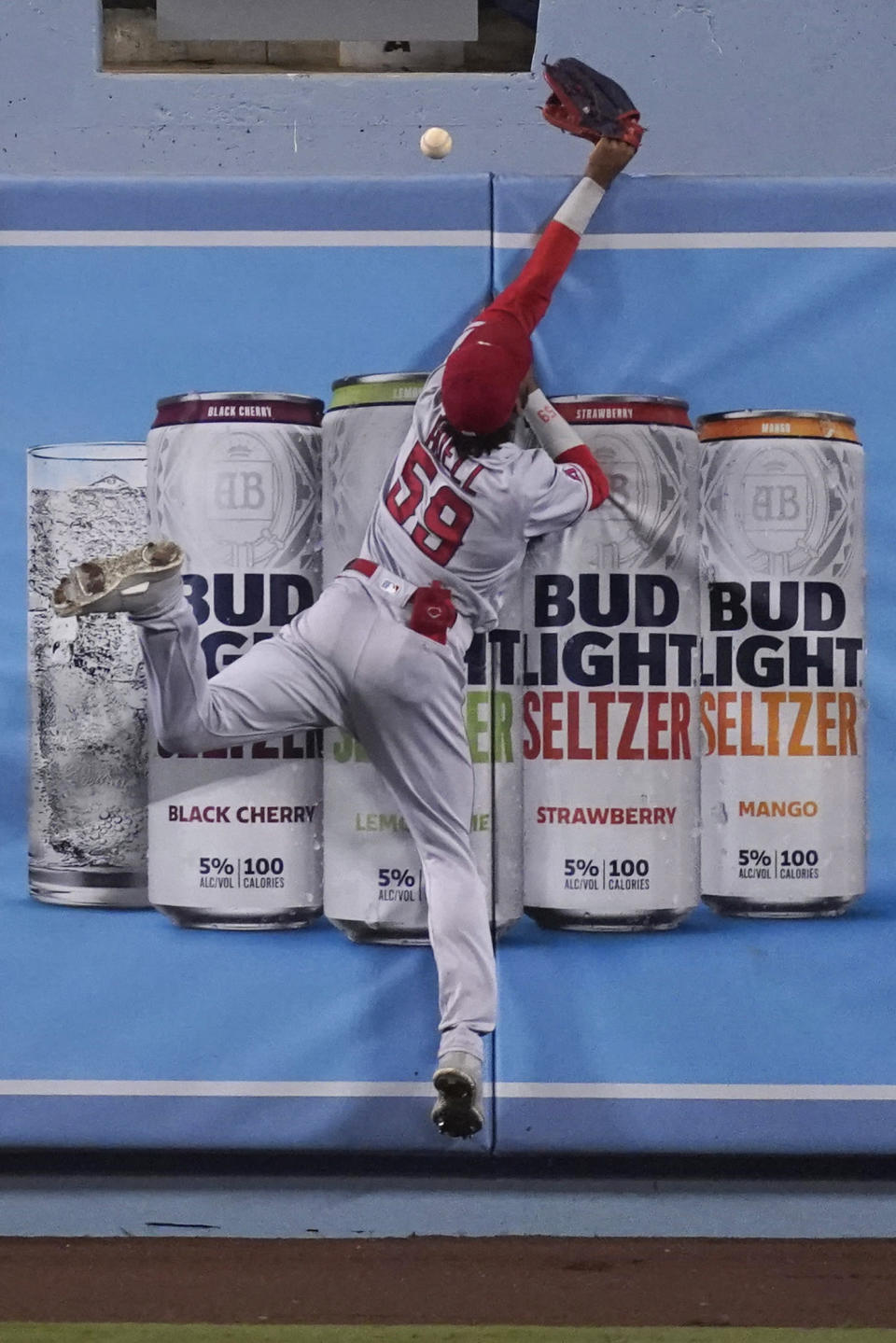 Los Angeles Angels center fielder Jo Adell can't make a catch on a home run by Los Angeles Dodgers' Edwin Rios during the seventh inning of a baseball game Saturday, Sept. 26, 2020, in Los Angeles. (AP Photo/Ashley Landis)
