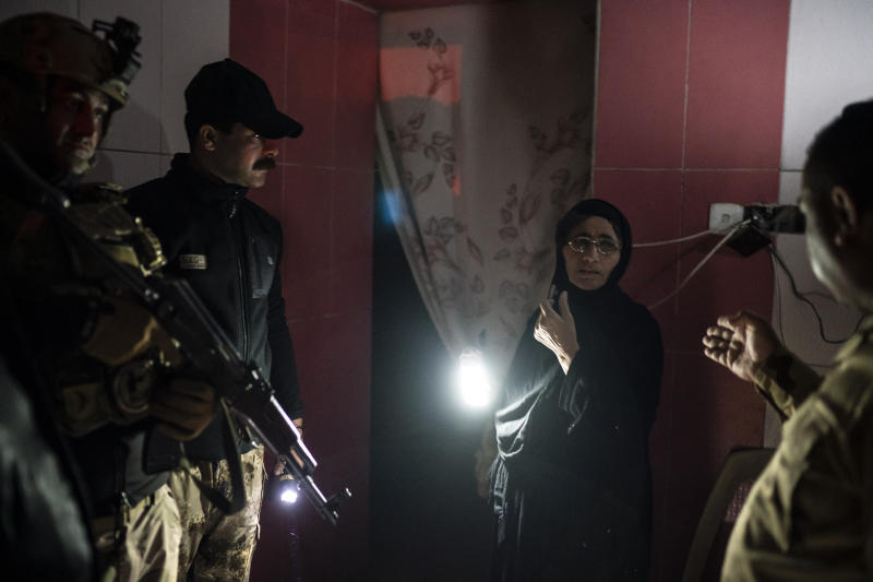 In this April 2, 2019 photo, Iraqi army 20th division soldiers talk to a woman during a nighttime raid near Badoush, Iraq. In towns around the north, Iraqi soldiers knock on doors in the middle of the night, looking for Islamic State suspects, based on intelligence tips or suspicious movements. They search houses and pull people away for questioning. (AP Photo/Felipe Dana)