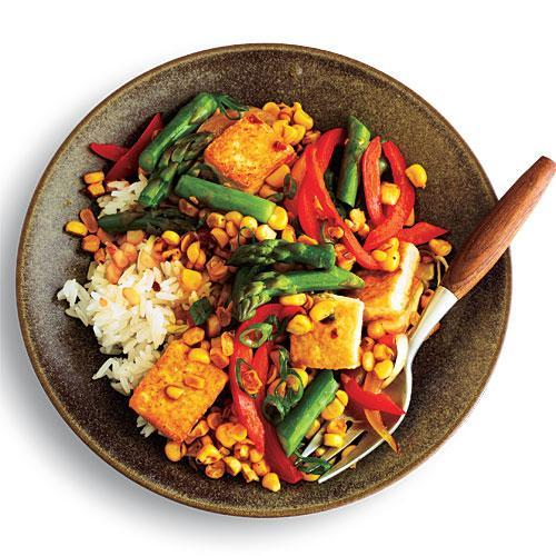 """<p>Rice and corn make a perfect bed for this bowlful of delicious flavor. Tofu makes this a filling meal.</p> <p> <a rel=""""nofollow noopener"""" href=""""http://www.myrecipes.com/recipe/ginger-corn-asparagus-stir-fry"""" target=""""_blank"""" data-ylk=""""slk:View Recipe: Ginger-Scented Corn and Asparagus Stir-Fry"""" class=""""link rapid-noclick-resp"""">View Recipe: Ginger-Scented Corn and Asparagus Stir-Fry</a></p>"""