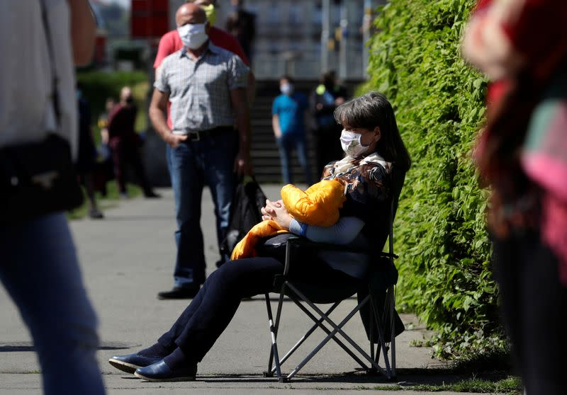 A woman sits on a chair while waiting in line in Prgaue