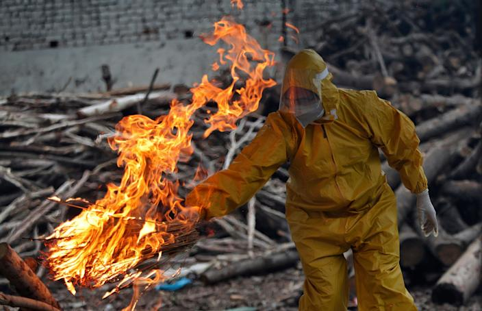 A family member of a person who died of Covid-19 lights the funeral pyre at a crematorium in Jammu (AP)