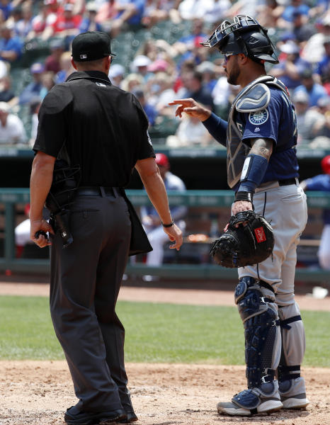 Home plate umpire Will Little looks on as Seattle Mariners catcher Omar Narvaez, who was hit by a pitch in the left leg, gestures to the mound in the third inning of a baseball game against the Texas Rangers in Arlington, Texas, Wednesday, May 22, 2019. Narvaez finished out the third but did not return in the fourth, leaving the game with an unknown injury. (AP Photo/Tony Gutierrez)