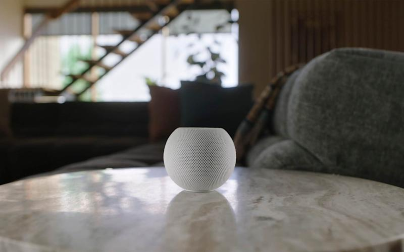 An Apple HomePod Mini sits alone in the centre of a marble-effect table, somewhere in the midst of a stylish modernist home, looking like some alien still life. The device itself is a little ball with the top few centimeters sliced off, with its outer skin a kind of web or knit of white filaments criss-crossing in a diamond pattern - Apple/AP