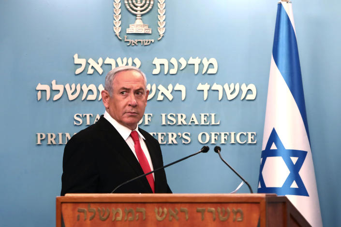 Prime Minister Benjamin Netanyahu approaches the podium to speak from his Jerusalem office on Saturday, March 14, 2020, saying Israel's restaurants and places of entertainment will be closed to stop the spread of the coronavirus. He also encouraged people not to go to their workplaces unless absolutely necessary. (Gali Tibbon/Pool via AP)