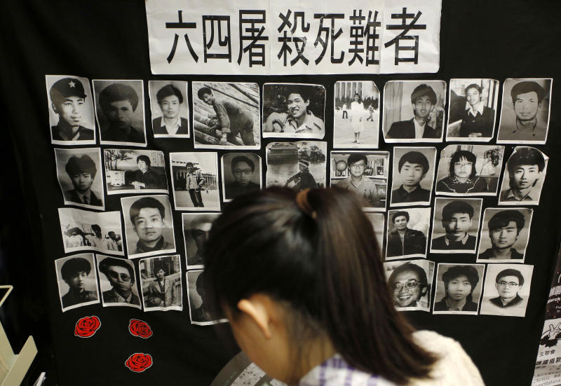 """A woman reads a book in front of portraits of victims of the crackdown of the June 4, 1989 pro-democracy movement in Beijing's Tiananmen Square at the """"June 4 Memorial Museum"""" run by pro-democracy activists at City University in Hong Kong Monday, June 3, 2013 to commemorate the 24rd anniversary of the bloodshed. Tens of thousands of protesters expected to attend a candlelight vigil at Hong Kong's Victoria Park in the evening of June 4. (AP Photo/Vincent Yu)"""