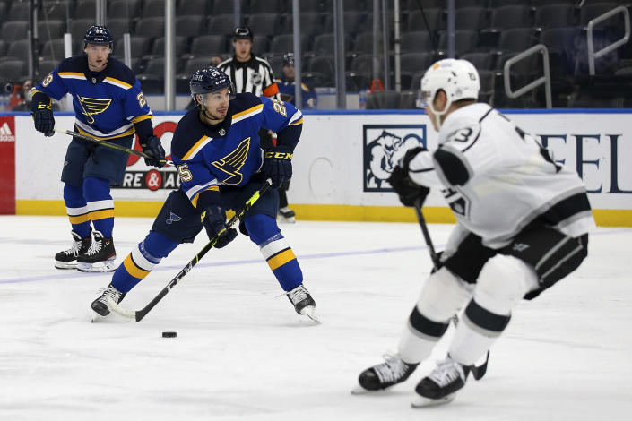 St. Louis Blues' Jordan Kyrou (25) handles the puck while Los Angeles Kings' Tobias Bjornfot (33) defends during the second period of an NHL hockey game Wednesday, Feb. 24, 2021, in St. Louis. (AP Photo/Scott Kane)