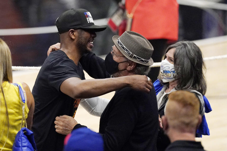 Phoenix Suns guard Chris Paul, left, hugs actor Billy Crystal, center, as Crystal's wife Janice stands by after the Suns won Game 6 of the NBA basketball Western Conference Finals against the Los Angeles Clippers Wednesday, June 30, 2021, in Los Angeles. The Suns won the game 130-103 to take the series 4-2. (AP Photo/Mark J. Terrill)