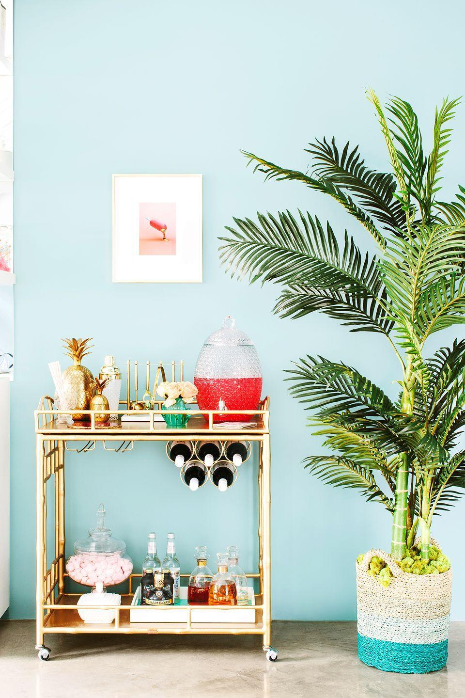 <p>Introduce a tropical vibe into your home by sprucing up your bar cart with beachy cocktails, gold decorative accents, and pretty florals. </p>