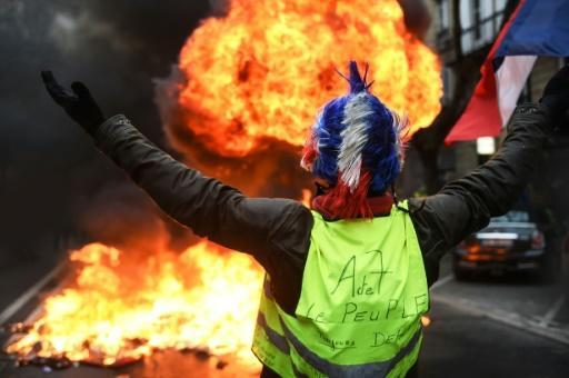 A yellow vest demonstrator holds up the French flag as he stands in front of a fire during protests in the western city of Bordeaux