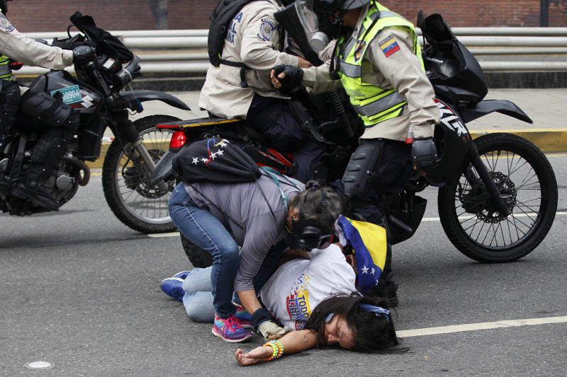A woman is aided by a fellow anti-government protester during clashes with security forces in Caracas, Venezuela, Thursday, April 20, 2017. Venezuela's opposition looks to keep up pressure on President Nicolas Maduro, taking to the streets again one day after three people were killed and hundreds arrested in the biggest anti-government demonstrations in years. (AP Photo/Ariana Cubillos)