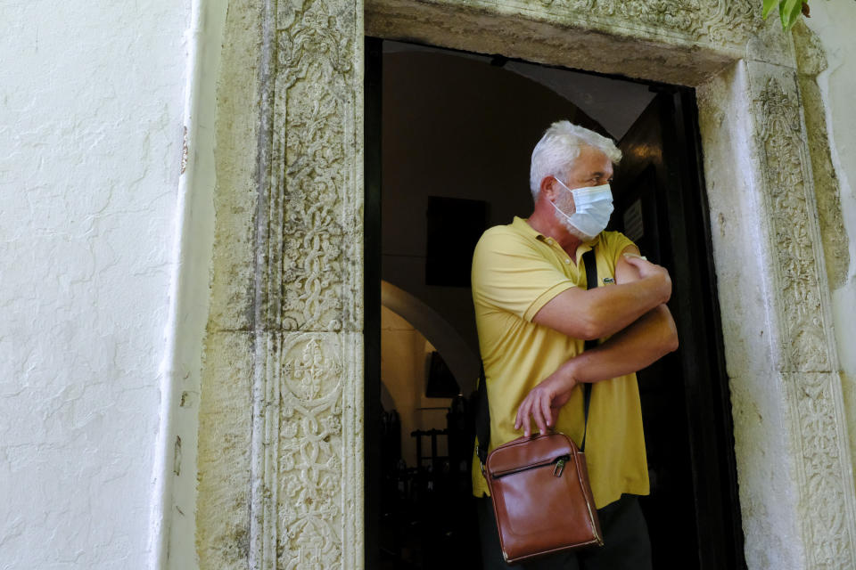 A man, who received the Johnson and Johnson COVID-19 vaccine, walks outside the church of the Virgin Mary, during a vaccination roll out, in the town of Archanes, on the island of Crete, Greece, Monday, Sept. 6, 2021. Greece has begun administering vaccinations for COVID-19 outside churches. It's a pilot program that was recently announced by the government as a means of encouraging more people to get the shots. Mobile National Health Organization units began administering shots Monday in a church yard in the town of Archanes near the city of Heraklion on the southern island of Crete. (AP Photo/Michael Varaklas)