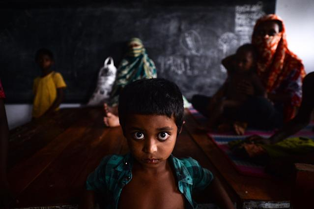 """A young resident rests with others in a shelter ahead of the expected landfall of cyclone Amphan in Dacope of Khulna district on May 20, 2020. - Several million people were taking shelter and praying for the best on Wednesday as the Bay of Bengal's fiercest cyclone in decades roared towards Bangladesh and eastern India, with forecasts of a potentially devastating and deadly storm surge. Authorities have scrambled to evacuate low lying areas in the path of Amphan, which is only the second """"super cyclone"""" to form in the northeastern Indian Ocean since records began. (Photo by Munir Uz zaman / AFP) (Photo by MUNIR UZ ZAMAN/AFP via Getty Images)"""