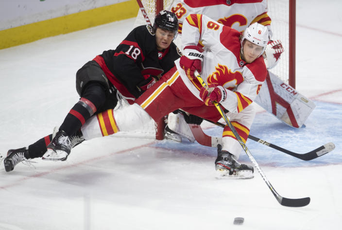 Calgary Flames defenceman Juuso Valimaki battles with Ottawa Senators left wing Tim Stutzle in front of the net during the second period of an NHL hockey game Thursday, Feb. 25, 2021, in Ottawa, Ontario. (Adrian Wyld/The Canadian Press via AP)