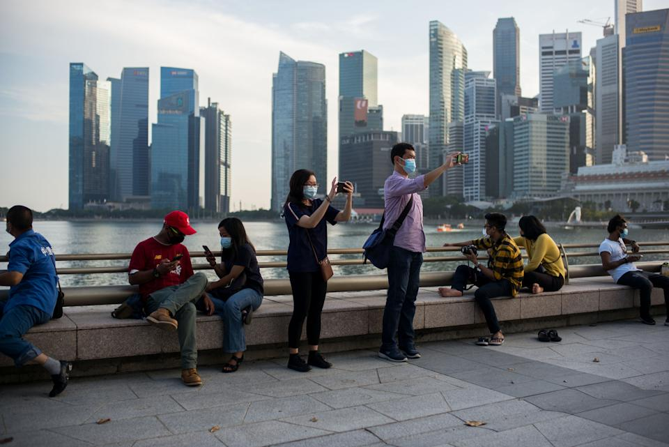 SINGAPORE - 2020/08/09: People wearing face masks as a preventive measure take pictures by the Singapore River, overlooking the central business district, during the Singapore National Day. Singapore celebrates its 55th National Day on the 9th of August 2020 amid the Covid-19 pandemic. (Photo by Maverick Asio/SOPA Images/LightRocket via Getty Images)