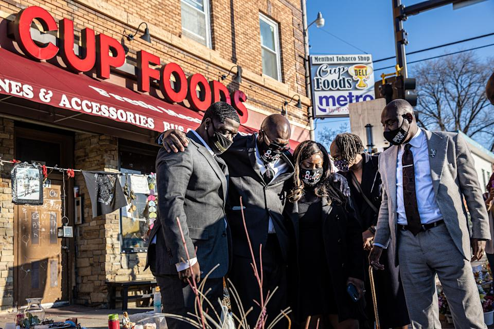 Family members of George Floyd, Brandon Williams (L),  Philonese Floyd (2nd L), Keeta Floyd (3rd L), and Floyd family attorney Ben Crump (C) visit a memorial at the site where George Floyd died while being arrested, after attending a press conference on March 12, 2021 in Minneapolis, Minnesota. - The Minnesota city of Minneapolis reached a $27 million
