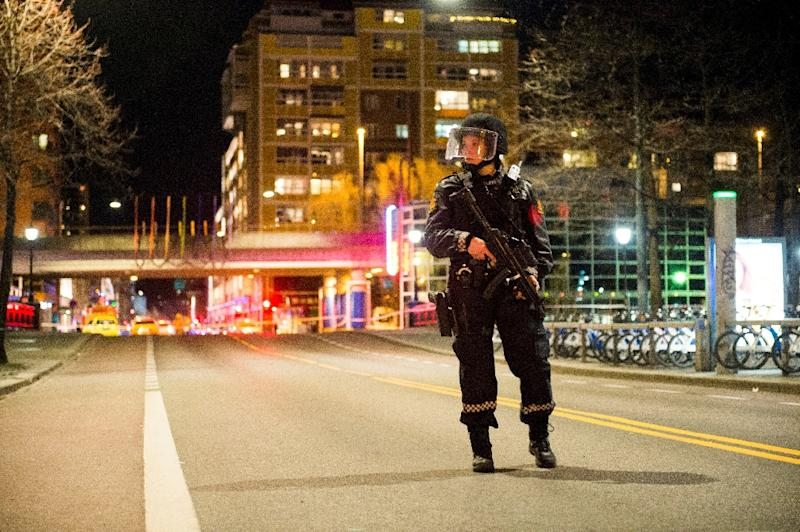 A police officer stands guard near a cordened off area in central Oslo on late April 8, 2017, following the discovery of a 'bomb-like device'