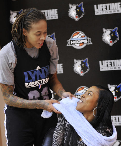 In this photo made Friday, Oct. 12, 2012, Minnesota Lynx WNBA basketball star and Olympic gold medalist Seimone Augustus jokes around with LaTaya Varner, right, in between interviews the two had with The Associated Press about their relationship and engagement. With a wedding scheduled for May and a crucial vote in November that threatens to ban gay marriage in Minnesota, the intensely private Augustus is speaking out. (AP Photo/Jim Mone)
