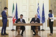 Greek Foreign Minister Nikos Dendias, right, and his Italian counterpart Luigi Di Maio asign an agreement following their meeting ,in Athens, on Tuesday, June 9, 2020. Greece will lift all restrictions on Italian tourists entering the country gradually between June 15 and the end of the month, Greece's foreign minister said Tuesday.(Costas Baltas /Pool via AP)