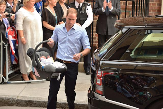 The Duke of Cambridge carries his new son, Prince George to the car. (Press Association)