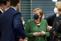 From left, German Economic Cooperation and Development Minister Gerd Mueller, German Health Minister Jens Spahn, German Chancellor Angela Merkel and German Science and Education Minister Anja Karliczek talk as they arrive for the weekly cabinet meeting at the Chancellery in Berlin, Germany, Wednesday, May 12, 2021. (AP Photo/Michael Sohn, pool)