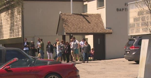 Congregants are seen gathered outside of the Fairview Baptist Church in southeast Calgary on Sunday, shortly before the arrest of Pastor Tim Stephens.