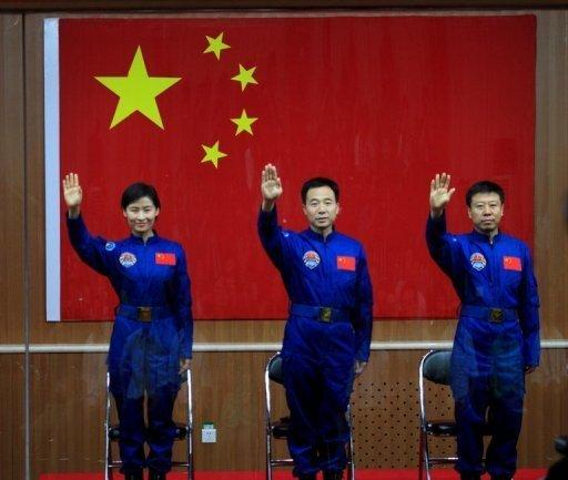 Chinese first woman astronaut Liu Yang together with her two male colleagues, Jing Haipeng (centre) and Liu Wang wave as they are introduced during a press conference at the Jiuquan space base in Gansu province. China launched its most ambitious space mission to date, sending its first female astronaut to the final frontier and bidding to achieve the country's first manual space docking