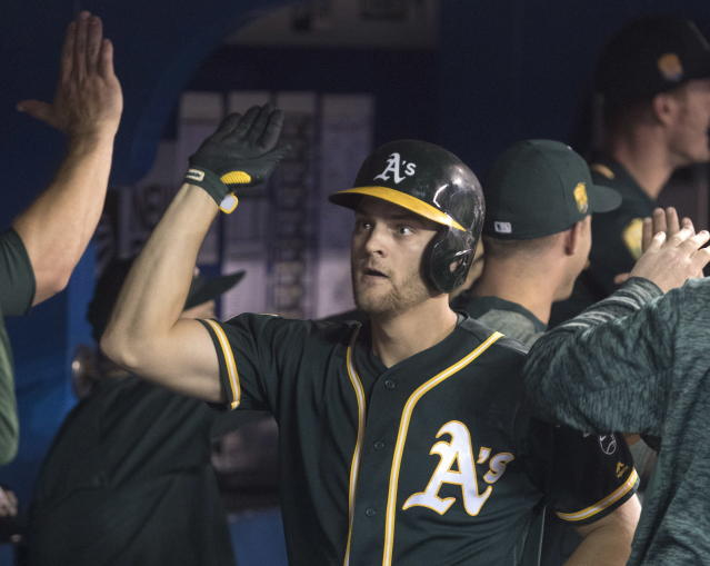 Oakland Athletics' Chad Pinder celebrates in the dugout after hitting a grand slam against the Toronto Blue Jays in the eighth inning of a baseball game in Toronto, Saturday, May 19, 2018. (Fred Thornhill/The Canadian Press via AP)