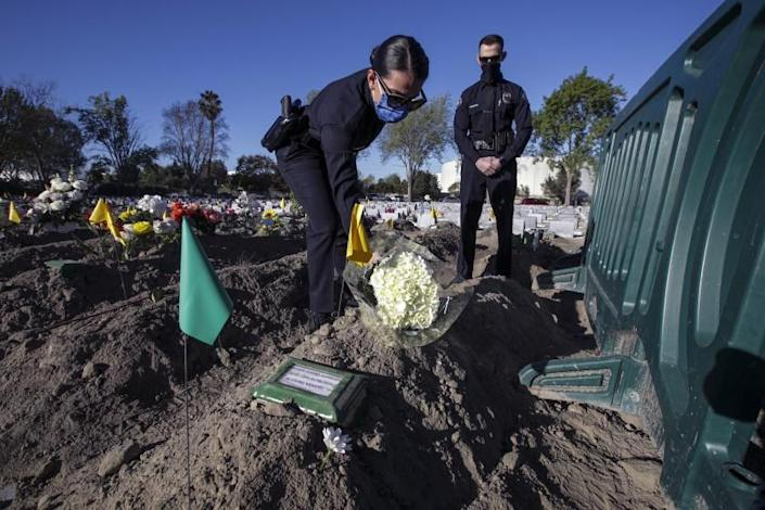Westminster, CA - January 14: Rayah Alshilleh, left, flanked by brother Mahmoud places flowers at the grave of their father Hashem Ahmad Alshilleh at Westminster Memorial Park Mortuary on Thursday, Jan. 14, 2021 in Westminster, CA. (Irfan Khan / Los Angeles Times)