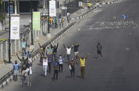 People demonstrate on the street to protest against police brutality in Lagos, Nigeria, Wednesday Oct. 21, 2020. After 13 days of protests against alleged police brutality, authorities have imposed a 24-hour curfew in Lagos, Nigeria's largest city, as moves are made to stop growing violence. ( AP Photo/Sunday Alamba)