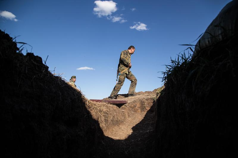 A Ukrainian serviceman walks past a trench on the front line near Lugansk during shelling on August 26, 2014 (AFP Photo/Oleksandr Ratushniak)