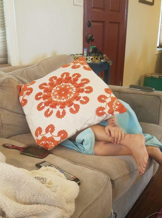 little girl covering face with a pillow