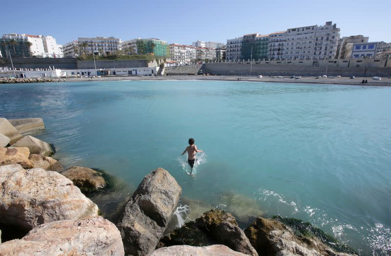 A boy plays in the water at a beach in Algiers