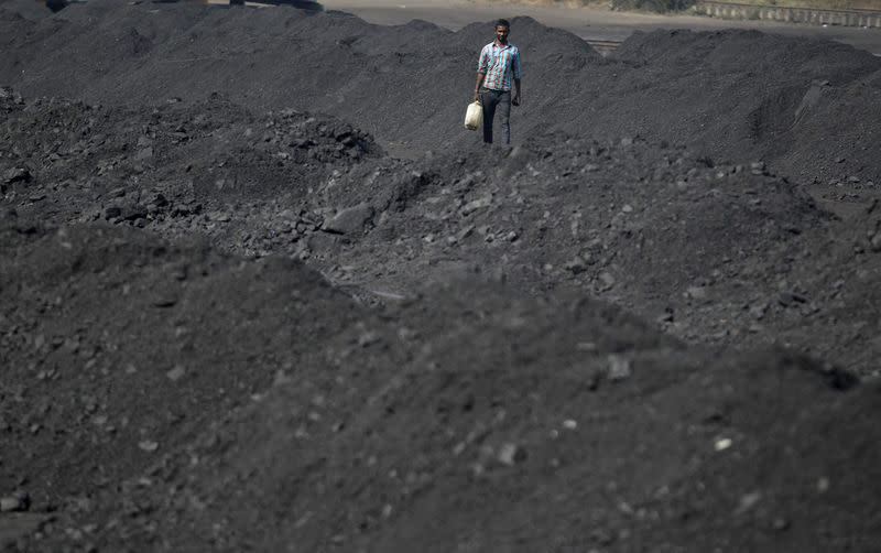 A worker carries a container filled with drinking water at a railway coal yard on the outskirts of Ahmedabad