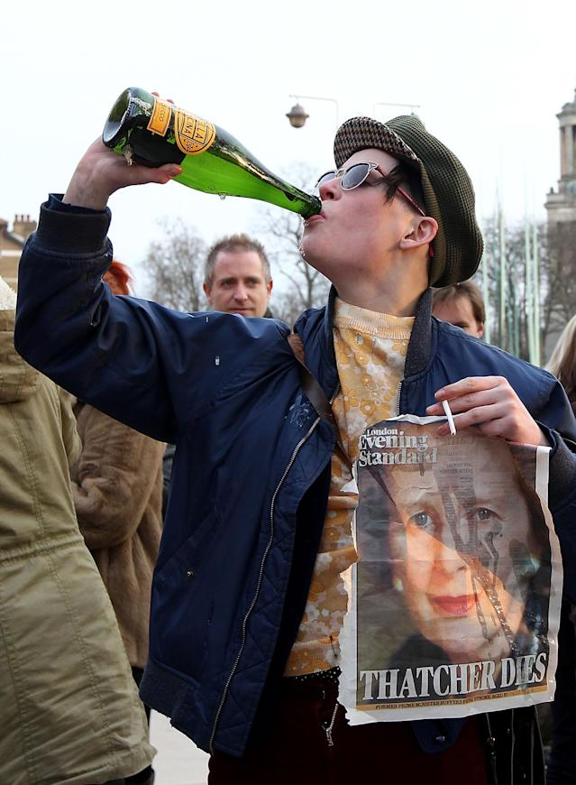 LONDON, UNITED KINGDOM - APRIL 08: A lady drinks from a bottle and holds a front page of a newspaper displaying an image of former Prime Minister Margaret Thatcher as she and others celebrate her death in Brixton on April 8, 2013 in London, England. Lady Thatcher has died this morning following a stroke aged 87. Margaret Thatcher was the first female British Prime Minster and governed the UK from 1979 to 1990. She led the UK through some turbulent years and contentious issues including the Falklands War, the miners' strike and the Poll Tax riots. (Photo by Danny E. Martindale/Getty Images)