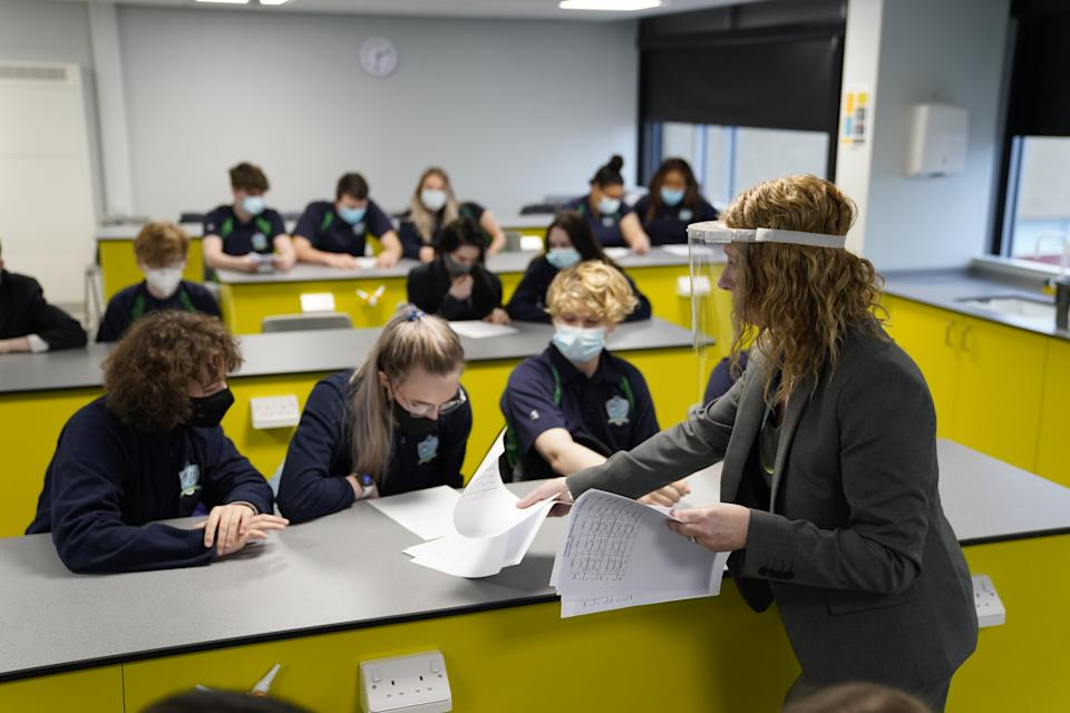 Children and teacher in Year 11 wearing facemasks during lesson at Our Lady and St Bede Catholic Academy in Stockton-on-Tees in County Durham, as pupils in England return to school for the first time in two months as part of the first stage of lockdown easing. Picture date: Monday March 8, 2021.