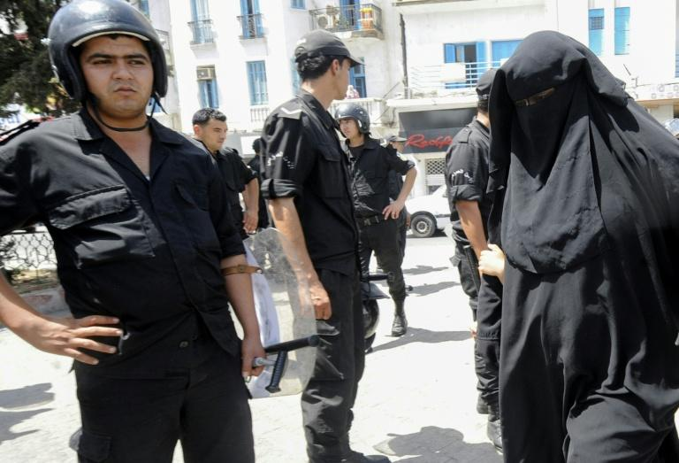 In this file photo from June 2012, a Tunisian woman, wearing a niqab, walks in front of police officers after Friday prayers