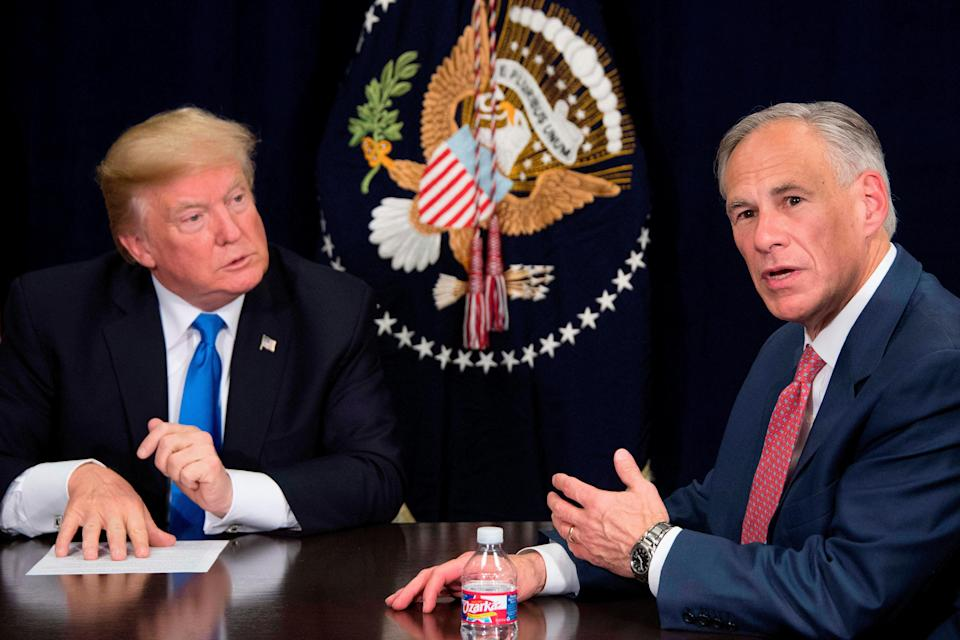 Texas Governor Greg Abbott (right) speaks with then-US President Donald Trump (left) during a briefing on hurricane relief efforts in Dallas, Texas, on 25 October, 2017. Mr Abbott has said he plans to raise funds to build more border wall between the US and Mexico. (AFP via Getty Images)