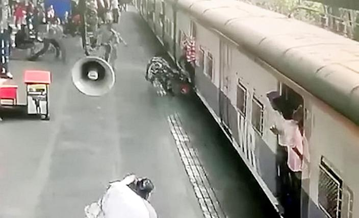 Police officer Sachin Pol rushes in to pull the girl to safety (Picture: SWNS)