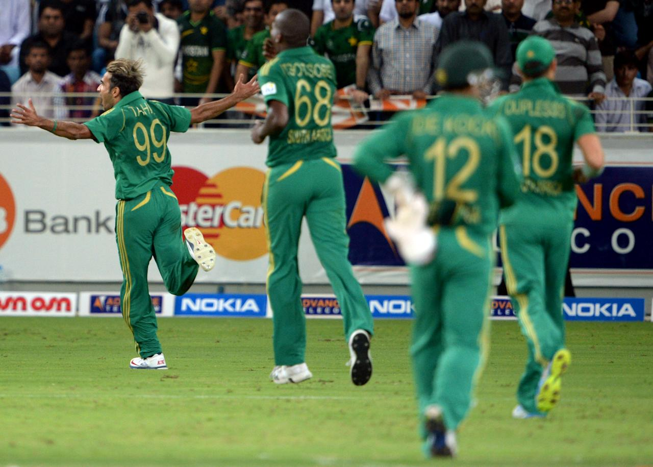 South African bowler Imran Tahir (L) celebrates after he clean bowled of Pakistani batsman Sohail Tanvir (unseen) during the second and last cricket T20 International at Dubai stadium on November 15, 2013 in Dubai. South Africa sparked another Pakistan batting collapse to win the second Twenty20 international by six runs, taking the two-match series 2-0. AFP PHOTO/ Asif HASSAN        (Photo credit should read ASIF HASSAN/AFP/Getty Images)