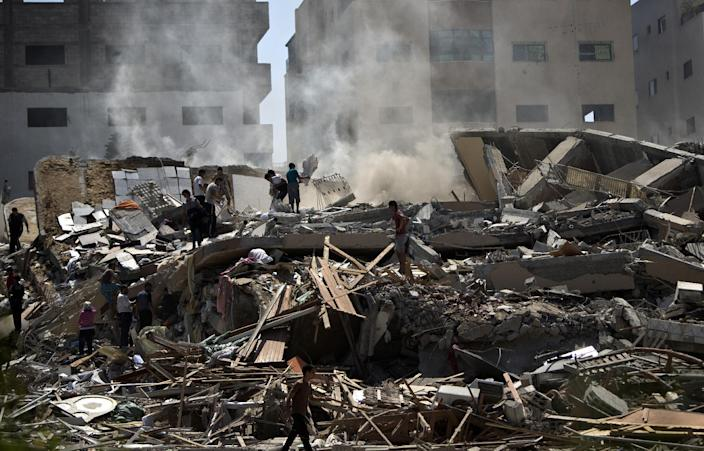 Palestinians on August 24, 2014 look through the rubble of a 12-storey apartment building that was hit by an Israeli air strike in Gaza City the day before (AFP Photo/Mahmud Hams)