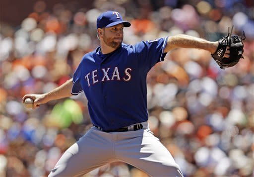 Texas Rangers relief pitcher Scott Feldman throws to the San Francisco Giants during the first inning of a baseball game in San Francisco, Saturday, June 9, 2012. (AP Photo/Marcio Jose Sanchez)