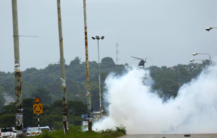 A helicopter fires teargas onto protestors during a demonstration over the hike in fuel prices in Harare, Zimbabwe, Tuesday, Jan. 15, 2019. A Zimbabwean military helicopter on Tuesday fired tear gas at demonstrators blocking a road and burning tires in the capital on a second day of deadly protests after the government more than doubled the price of fuel in the economically shattered country. (AP Photo/Tsvangirayi Mukwazhi)
