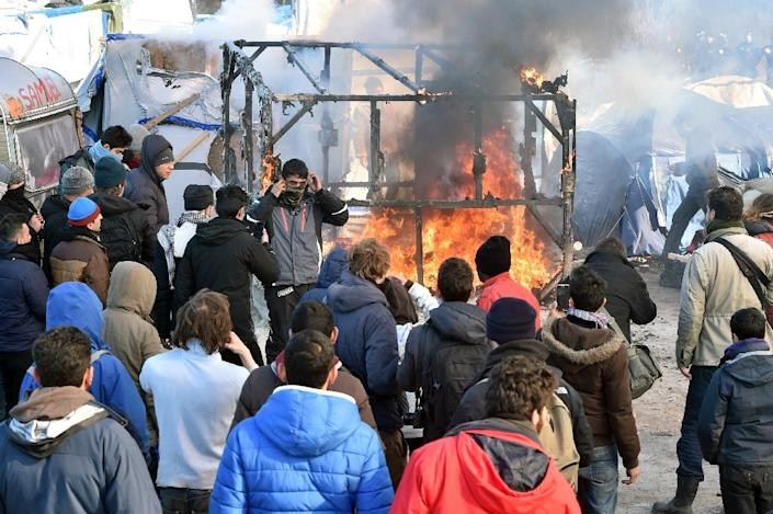 """A shack burns in the """"Jungle"""" migrant camp in the French city of Calais on February 29, 2016 (AFP Photo/Philippe Huguen)"""