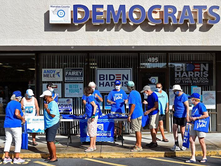 """Bob McCaa, in center, coordinating volunteers at the Manatee County Democratic Party headquarters on Wednesday afternoon, Oct. 28, 2020. Here volunteers prepare to head out into Bradenton area neighborhoods to drop off voting information about the candidates. It's a """"no knock"""" no contact door-to-door canvassing effort to get the people out to vote."""